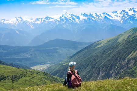 A young girl with a backpack sits on the top of a mountain in Georgia and contemplates the landscape. The traveler made the climb. Hiker relax and looking over horizon