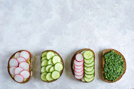 Homemade sandwiches with radish, pesto, cucumber and cheese on the gray background. Slices of vegetables on bread. Flat lay, top view, place for text. Reklamní fotografie