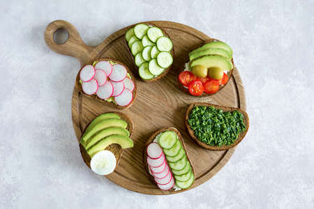 Vegetarian sandwiches on the wood board on the gray background. Fresh bread with pesto, cucumber, avocado, cherry tomatoes, radish and cheese. Flat lay, top view.