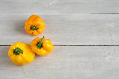 Shaped yellow bell peppers on the wooden white background. Misshapen produce, food waste problem concept. Trendy ugly food. Strange, imperfect organic vegetables. Horizontal, close up, top view