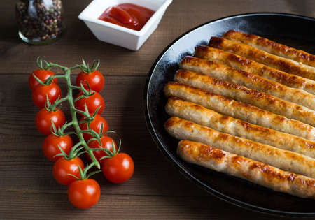 Roasted sausages on frying pan with fresh branch of cherry tomatoes on wooden background. 免版税图像