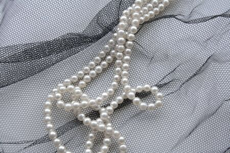 tulle: Necklace of pearls over black tulle