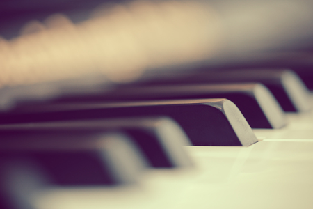 Closeup shot of piano keyboard. Vintage style with blurred background.