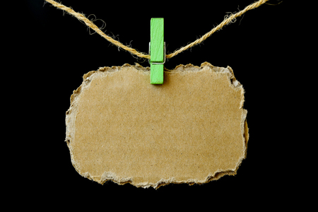 Blank brown paper hanging on rope with pin.