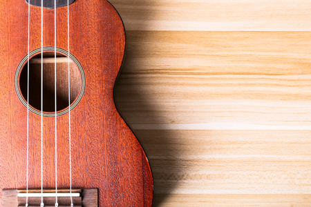 Ukulele on the wooden background with blank copy space.