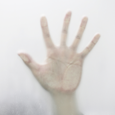 Shadow hands of the Man behind frosted glass. Stock Photo