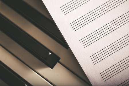 Close-up shot of blank music notes paper and piano keyboard Banque d'images
