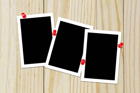 Some blank black photo pinned on the wood background