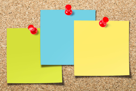 Cork board with three colorful blank sticky notes.