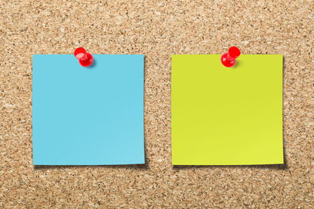 Cork board with two colorful blank sticky notes.