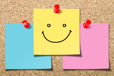 Cork board with three colorful sticky notes with smile face.