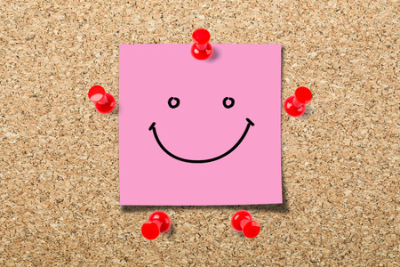 Cork board with a smile face sticky notes. Stock Photo