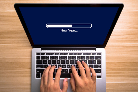 New Year Concept laptop screen with typing hands on the keyboard.