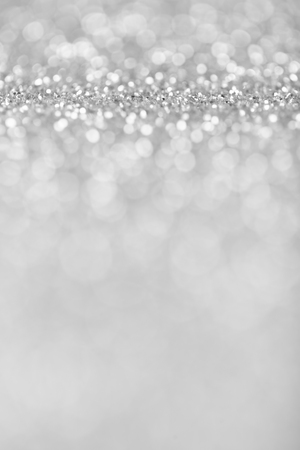 Abstract background of silver glittering defocused lights.