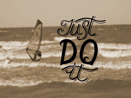 just do it: Hand lettering Just do it made on the background of the sea with a floating boat with a sail. Motivational quotes. Poster. Stock Photo