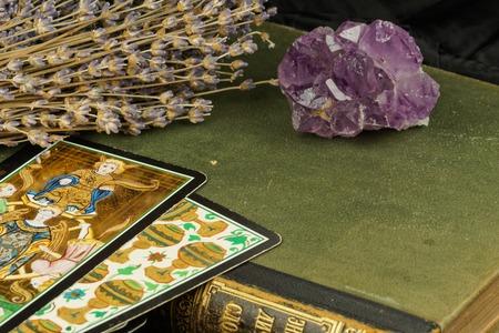 Amethist op een groen boek, de lavendel en tarotkaarten. Donkere achtergrond