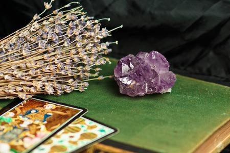 psychic: Amatista sobre un libro verde, la lavanda y las cartas del tarot. Fondo oscuro Foto de archivo