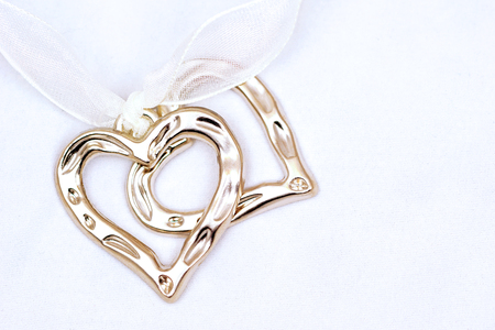 Two metal hearts on light background, template for postcard Standard-Bild
