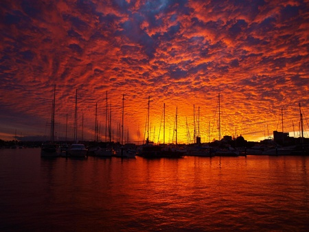 Stronly coloured blood red sunset highlighting Altocumulus cloud formation at a marina at Mooloolaba-Queensland-Australia -With water forground. Stock Photo - 9471212