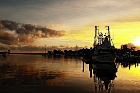 Fishing trawler silhouetted by a beautiful golden sunrise over waterthrough cloud with clear water reflections