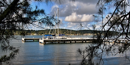 stock vista: F Jetty - Wharf at Lake Macquarie with trees in the foreground and a blue cloudy sky. New South Wales, Australia.Landscape, wharf, trees, water, waterscape, boats, scene, scenic, view, vista, panorama, sky, blue sky, cloud, color, colourful, horizon, ho Stock Photo