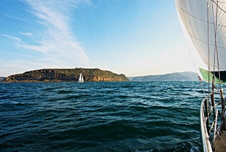 Cruising Sailing Yacht, under sail,  at sea heading to the safe harbour of Broken Bay, New South Wales, Australia. Stock Photo