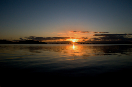 crimson colour: Gold and grey sunrise seascape with water reflections in the tranquil waters of Lake Macquarie at dawn. New South Wales, Australia.