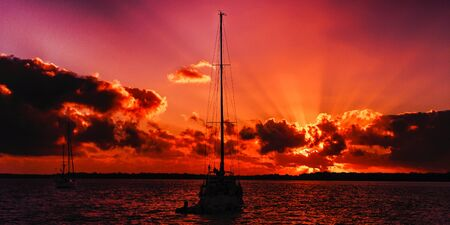 A striking inspirational red coloured cloudy sea water sunrise seascape featuring a sailing yacht in silhouette with ocean water reflections. Fraser Island, Queensland, Australia. Stock Photo