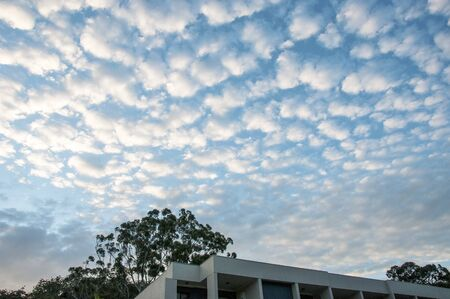 A spectacular inspirational brightly coloured atmospheric cloudy sky cloudscape featuring Cirrus cloud formation in a mid blue sky. Gosford, Australia.