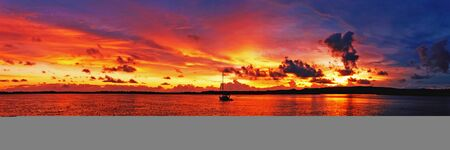 A spectacular inspirational brightly coloured cloudy sea water tropical panoramic sunrise seascape featuring silhouettes with ocean water reflections. Queensland, Australia.