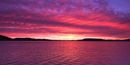 A magnificient panoramic inspirational magenta coloured altostratus cloudy sunrise seascape over sea water with water reflections. Gosford, New South Wales, Australia.