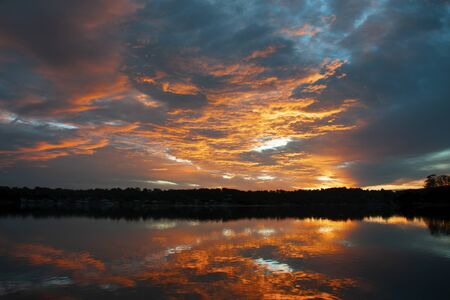A striking nature orange coloured stratocumulus cloudy coastal sunrise seascape over sea water with vibrant water reflections. Gosford, New South Wales, Australia. Stok Fotoğraf