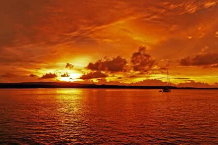A bright inspirational panoramic orange coloured cumulus cloudy sunrise seascape over sea water with water reflections. Nautical beauty in nature background image. Queensland, Australia. Stok Fotoğraf