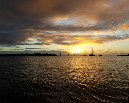A vibrant nautical golden-yellow coloured nimbostratus cloudy sunrise seascape over sea water with water reflections and a distant sailboat. Queensland, Australia.