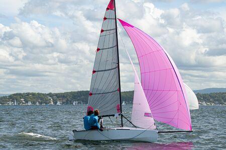 Zwei Schulkinder segeln ein kleines Segelboot mit einem voll ausgefahrenen, leuchtend rosa Spinnaker zum Spaß und im Wettkampf. Teamwork von Junior-Seglern, die auf dem Salzwassersee Macquarie Rennen fahren. Foto für kommerzielle Nutzung. Standard-Bild