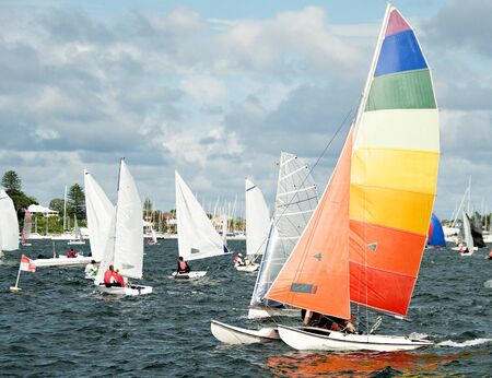 Racing Cat sailboat closeup with a bright multicoloured sail competing in a junior sailing regatta. Australia. Commercial use photo. Teamwork by young sailors. Lake Macquarie, Australia. Photo for commercial use. Zdjęcie Seryjne