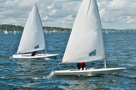 Children sailing in small colourful boats and dinghies for fun and in competition. Teamwork by junior sailors racing on saltwater Lake Macquarie. Photo for commercial use. Stock fotó