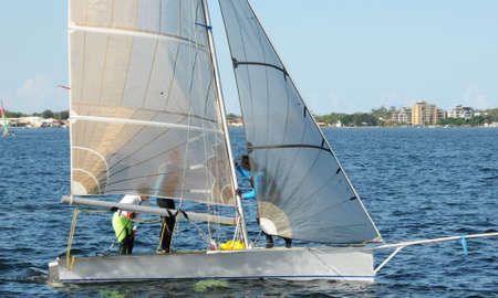 Children sailing small dinghy with white sails up-close on an inland waterway. Teamwork by junior sailors racing on saltwater Lake Macquarie. Photo for commercial use.