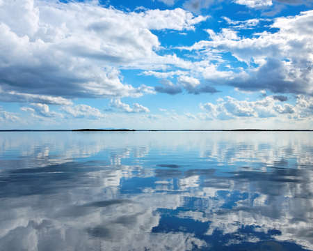Nephology at its best. A beautiful meteorological sky cloudscape scene, with white Cumulus cloud formation in a mid blue sky over ocean water with reflections. Seascape beauty in nature. New South Wales, Australia.