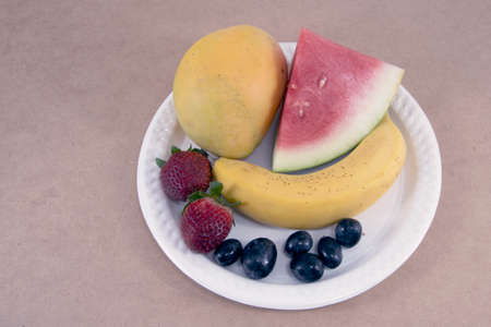 Colourful fresh tropical fruits including strawberry banana on a white plate isolated on a light beige background. Closeup top view.