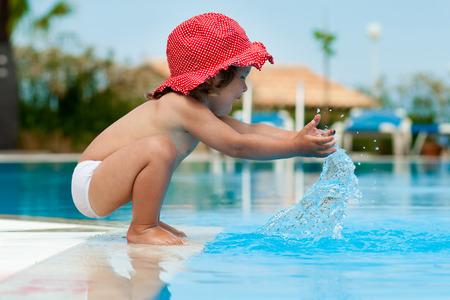 nadar: Ni�a divertida que se divierte con un toque cerca de la piscina Foto de archivo