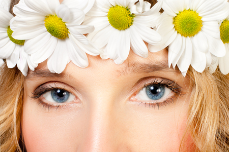 faultless: Close-up image of a womans beautiful blue eyes with chamomile wreath Stock Photo