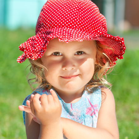 sunhat: Portrait of smiling little girl in red sunhat outdoors
