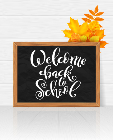 Welcome back to school hand-drawn lettering background. Realistic blackboard with autumn leaves. Vector illustration