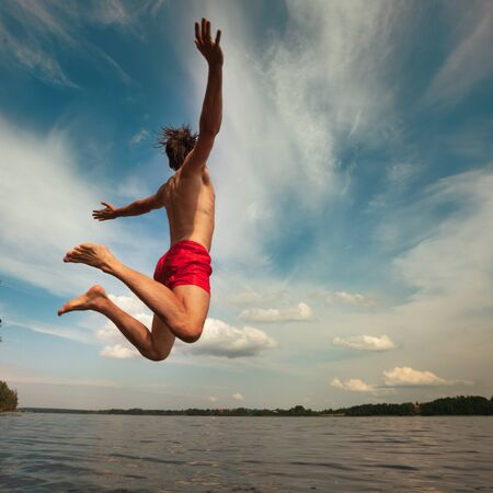 Young man jumping into water. Outdoor adventure lifestyle.