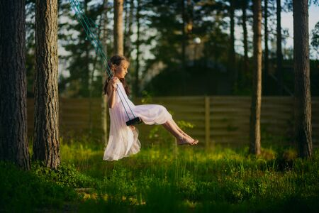 Happy child girl on swing in pink dress in the forest. Summertime.