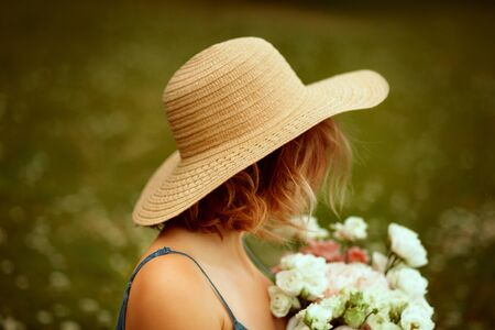 Portrait of young beautiful girl with curly hair from the back in the summer hat keepings flowers. Summertime.
