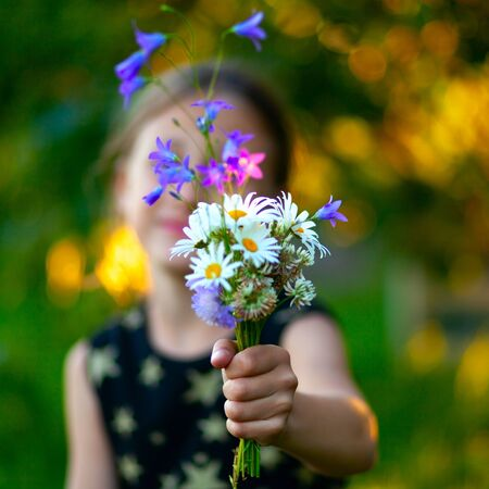 Little cute girl with bouquet of wildflowers. Child gives flowers to mom. Close up view on the hand with present. Stock fotó