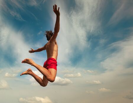 Man jumping over cloudly sky background. Summer fun lifestyle