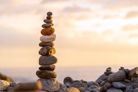 Balanced stone pyramide on shore of the ocean at dawn. Sea pebbles tower closeup symbolizing stability, zen, harmony, balance.